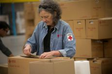 January 2, 2016 -- Arlington, Texas -- Photos from the massive ARC warehouse, one of five in the country storing clean up kits, cots, and other supplies commonly used in RC operations. ARC volunteer Susan Clark moves cleanup kits. Photos by Dennis Drenner for the American Red Cross.