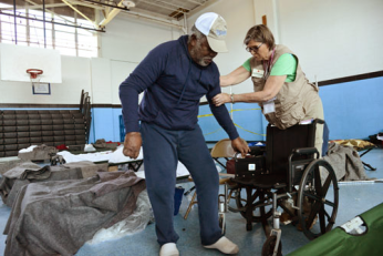 Red Cross nurse Joan assists Annias Baker into a wheel chair