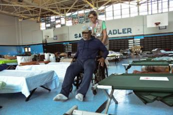 Red Cross nurse wheels Annia Baker through a shelter