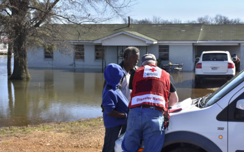 Paul Strickland and his son Paul Strickland, Jr. share their ordeal and complete paperwork with Red Cross caseworker Mike Peterson in front of his Robinsonville, Mississippi, home now surrounded by floodwaters.