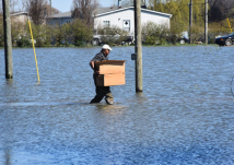 Robinsonville, Mississippi, resident Elvin Moore heads for his now flooded home with cleanup kits provided by the American Red Cross.