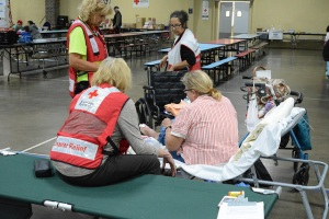 Red Cross volunteers work with a wheelchair bound client ensuring that all of her medical needs are met. Photo by Virginia Becker