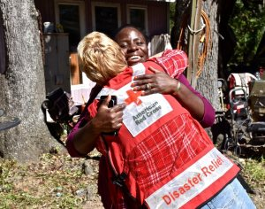 """High winds from  Hurricane Matthew brought down huge trees all around Shanta Millan's home on Edisto Island, but her home survived intact. """"Yes, we have storm damage, but we know how lucky we really are in life,"""" said Shanta as she gave Red Cross disaster responder Michelle Hankes  big hug. Photo Credit: Bob Wallace/American Red Cross"""