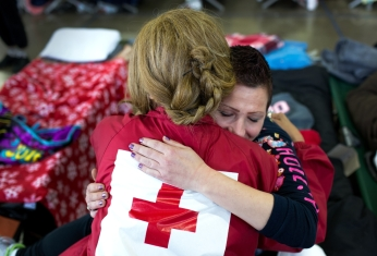 Sabreen and Emily meet and hug at a Red Cross shelter. Sabreen had to evacuate her home in Oroville and is staying in the shelter. Sabreen has also helped out at the shelter by running games and activities for the kids. Photo: Marko Kokic, American Red Cross