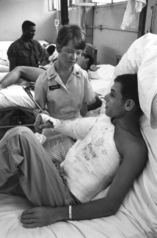 June 1968. Qui Nhon, South Vietnam. PROBLEMS HANDLED HERE . If a patient at the 67th Evacuation Hospital in Qui Nhon has a problem, he calls it to the attention of Red Cross hospital worker Evelyn Hardison. Here she is consulted by SP4 Irwin Cohen, who comes from San Francisco. Red Cross staffers provide sick and wounded servicemen at the 67th with non-medical personal attention and casework services, such as arranging emergency communications between a wounded man and his worried family at home. Photo by Mark Stevens/American Red Cross