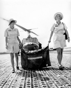 "November 1969. Tuy Hoa, Vietnam.""Toting equipment bag labeled 'the Age of Aquarius,' American Red Cross recreation workers Mary Gin Kennedy (left), Lewiston, Idaho, and Sharon Bernardi, Rt. 5, McAlester, Oklahoma, leave helicopter and head for outlying unit where they will present an informal recreation program. They are two of 110 Red Cross girls bringing recreation activities to U.S. troops in Southeast Asia."" Photo by by James Caccavo/American Red Cross."