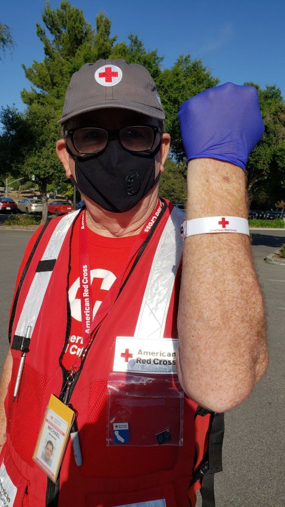 Red Cross volunteer Michael M. shows his wrist band that he received after completing his health screening.